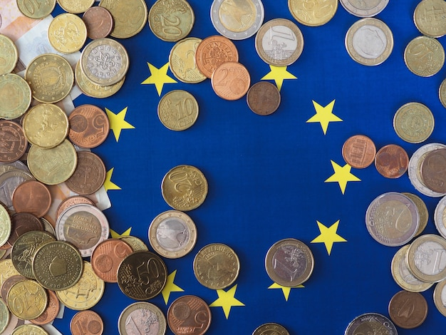 Euro coins (eur), currency of european union over flag of europe
