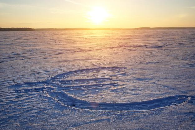 雪の上に描かれたユーロ通貨のアイコン。バックグラウンドでの夕日。
