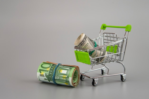 Euro and dolar banknotes in rolls with supermarket trolley on gray background