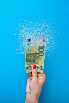 Инфляция евро. инфляция в европе, гиперинфляция. баннер с синим фоном. банкнота в сто евро распыляется в руке человека на синем фоне.