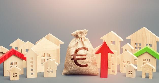 ユーロマネーバッグと家の街の数字と赤い上向き矢印。不動産価格の回復と成長