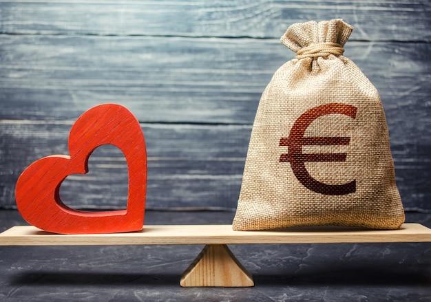 Мешок денег евро и красное сердце на весах. концепция финансирования страхования жизни.