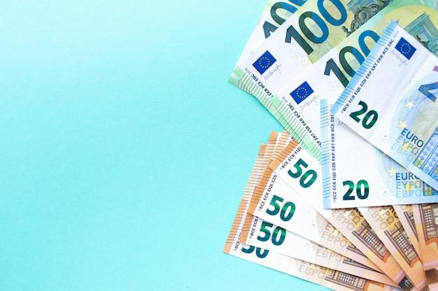 ユーロのお金。 100、50、20ユーロの紙幣は、右側の青色の背景に配置されています。テキストのための場所。お金と金融の概念。