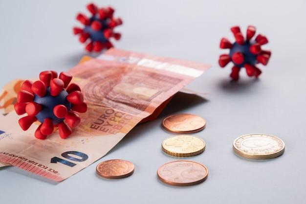Евро деньги, монеты и модели вируса ковид-19. зараженные деньги. кризис экономики