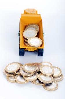 Monete e camion dei soldi dell'euro isolati su spazio bianco