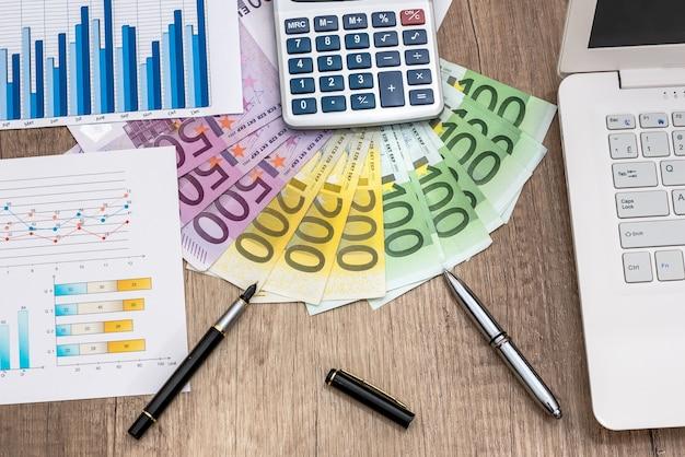 ラップト付きのユーロマネー、机の上のビジネスグラフ