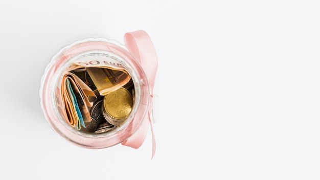 Euro notes and coins in glass jar tied with pink ribbon on white background