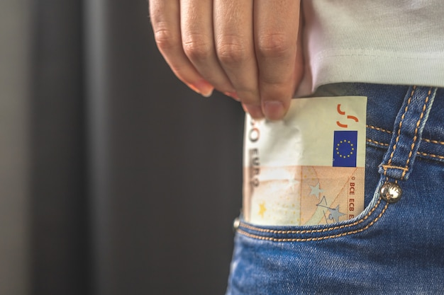 Euro in pocket. woman pulls out money from her jeans pocket, close-up view, copy space photo