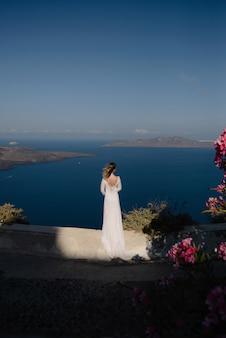 유럽 그리스 산토리니 여행 휴가. 유명한 여행 목적지에서보기를보고하는 여자. 휴일에 드레스를 입고 멋진 jetset 라이프 스타일을 살고 우아한 젊은 아가씨. 바다와 칼데라의 놀라운 전망