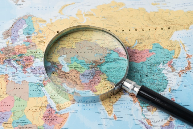 Europe, magnifying glass close up with colorful world map.