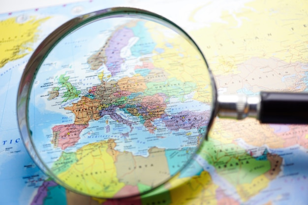 Europe : magnifying glass on world map background.
