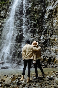 Europe travelers admire waterfall while on vacation