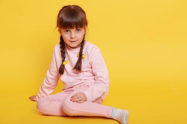 黄色の背景の上に隔離された淡いピンクのズボンとセーターを着て、床に座っているヨーロッパの愛らしい女の子は、カメラ、ピグテールを持つ黒髪の女性の子供を見ています。