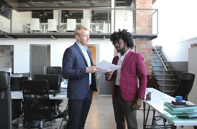비즈니스 회의 중에 계약을 논의하는 유럽 및 아프리카 계 미국인 비즈니스 파트너