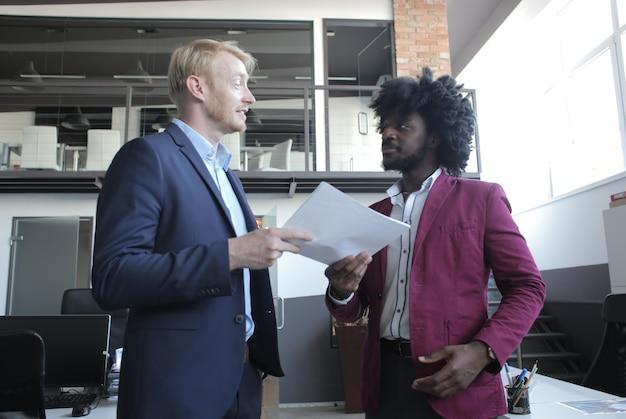ビジネスミーティング中に契約について話し合うヨーロッパおよびアフリカ系アメリカ人のビジネスパートナー