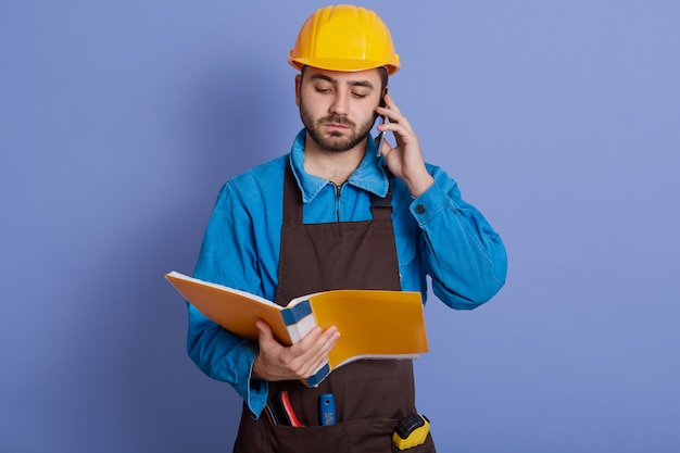 European architect with yellow paper folder in hands reading important information to his partner or bass, while talking via smart phone