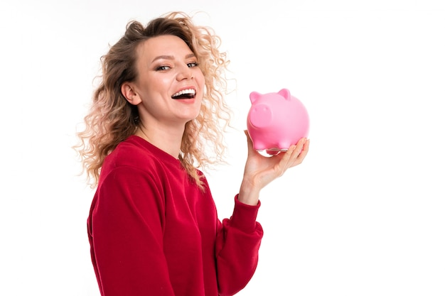 European attractive girl holds a piggy bank in hands on a white studio background with copyspace