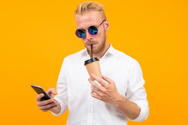 그의 손에 유리 흰색 클래식 셔츠에 유럽 매력적인 남자는 노란색에 전화를 찾습니다