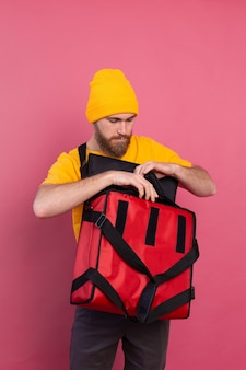 European bearded delivery man open box with food on pink