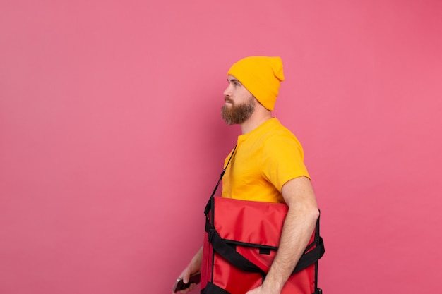 European bearded delivery man with box with food on pink