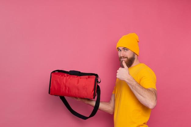 Uomo di consegna barbuto europeo con scatola con cibo sorridente e mostrando il pollice in alto sul rosa