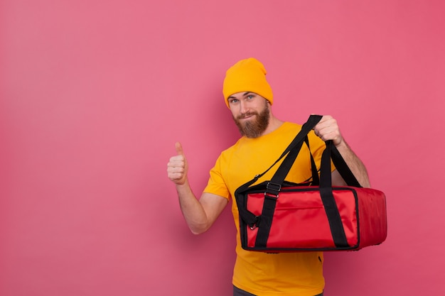 European bearded delivery man with box with food smiling and showing thumb up on pink