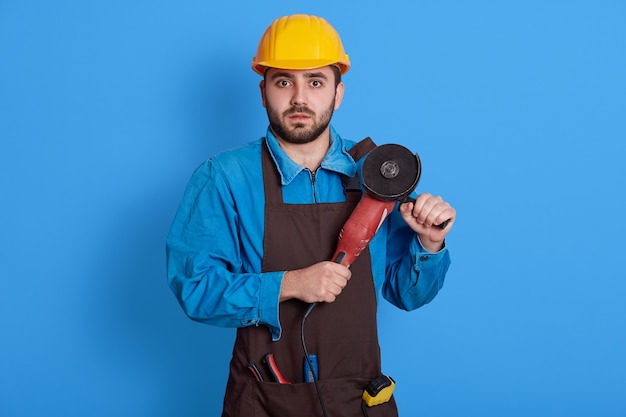 European bearded male builder or manual worker in yellow protective helmet and brown apron over blue wall, looks at camera with scared look,. construction, building.