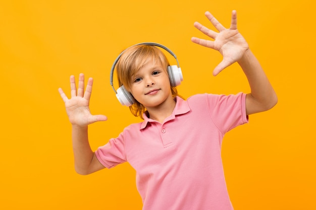 European blond boy in a pink t-shirt comes off to music in white headphones on orange