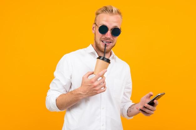전화와 한 잔의 커피 onyellow 스튜디오 유럽 금발 남자.