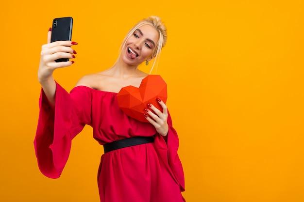 빨간 드레스에 유럽 금발의 젊은 여자 복사 공간 오렌지 스튜디오 표면에 종이로 만든 붉은 마음으로 전화에 셀카를 만든다