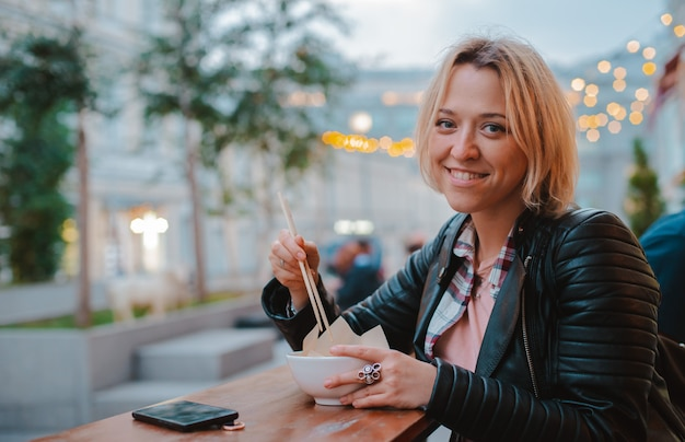 European blonde girl eating rice pho bo with wooden sticks table street vietnamese cafe in moscow.