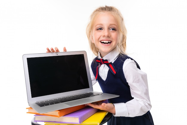 European blonde girl holds laptop with mockup on white wall