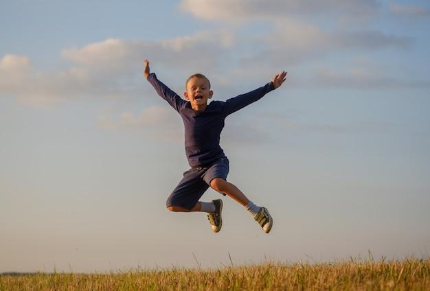 Европейский мальчик счастливо прыгает высоко в поле