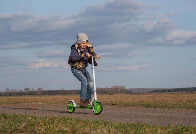 春に水たまりをスクーターに乗って楽しんでいるヨーロッパの少年