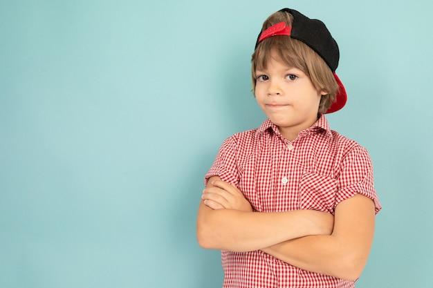 赤いシャツを着たヨーロッパの少年が腕を組んだ