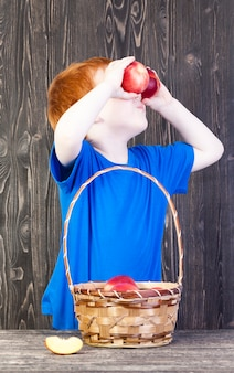 European boy playing with ripe nectarines, which he keeps before his eyes, closeup