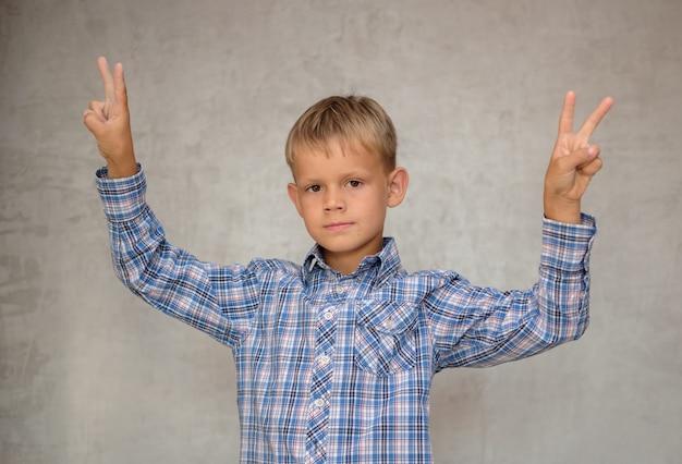 ヨーロッパの少年は灰色の壁に両手でビクトリアのジェスチャーを示しています