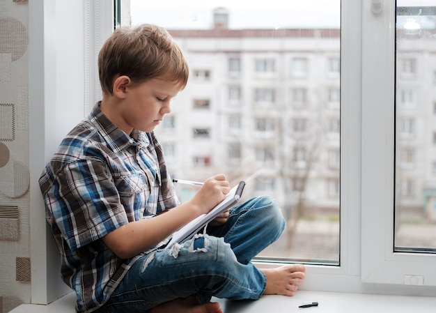 窓辺の窓辺に座ってノートに詩を書くヨーロッパの少年
