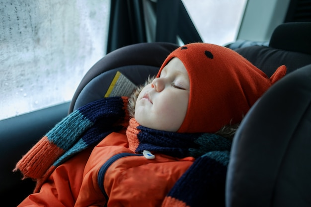 European boy sleeping in the car seat in the car in the winter in clothes