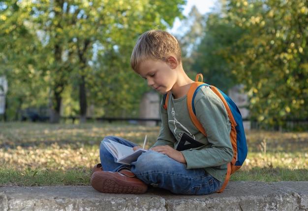 美しい秋の公園に座って、ノートで宿題をしているヨーロッパの少年学生