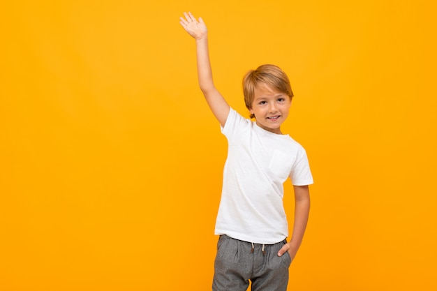 European boy in a white t-shirt with mockup with a raised hand on a yellow with copy space