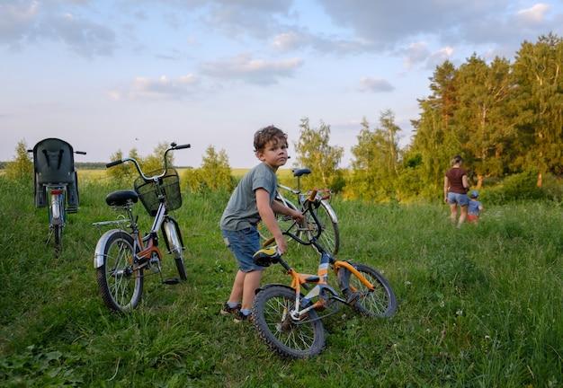 公園で夏に家族の自転車に乗っている間に自転車を持っているヨーロッパの少年