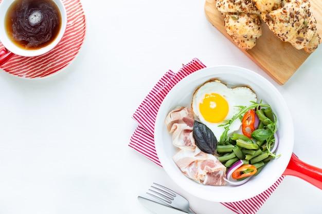 ヨーロッパの朝食:白いテーブルの上にハート型の卵、ベーコン、インゲン。セレクティブフォーカス。上からの眺め。スペースをコピーします。