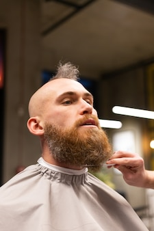 European brutal man with a beard cut in a barbershop