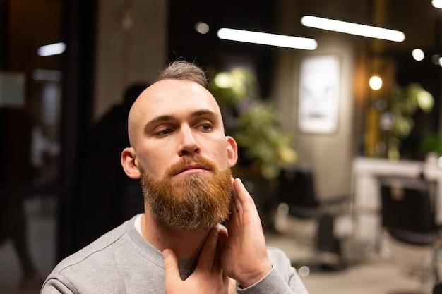 Uomo brutale europeo con una barba tagliata in un negozio di barbiere