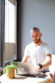 L'uomo d'affari europeo in camicia bianca fa lavoro a distanza