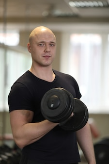 European caucasian athletic man bodybuilder in black sportwear holding dumbell and showing his muscular arms. man doing exercise for biceps