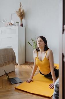 ヨーロッパの白人女性は、黄色いマットの上で彼女の家の家を落ち着かせるヨガでヨガと瞑想をします