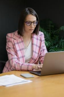 ピンクのジャケットを着て、彼女のオフィスでラップトップを持って働くヨーロッパの自信を持ってビジネス女性