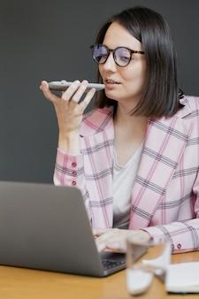 ピンクのジャケットを着て、彼女のオフィスでラップトップを持っているヨーロッパの自信を持ってビジネス女性